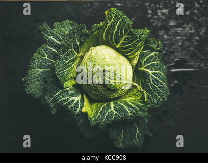 Raw fresh green cabbage over dark background
