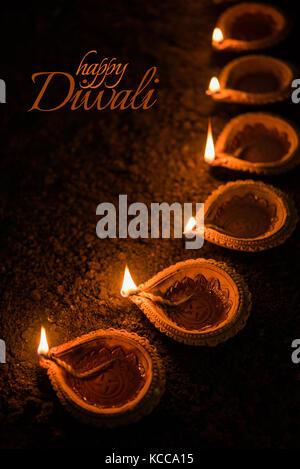 Happy Diwali greeting card design using Beautiful Clay diya lamps lit on diwali night Celebration.  Indian Hindu - Stock Photo