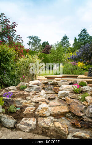 A newly planted rock garden after installing a hand-built natural stone waterfall in an English garden in UK - Stock Photo