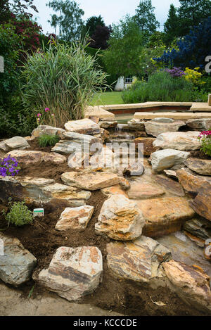 Planting a new rock garden after installing a hand-built natural stone waterfall in an English garden in UK - Stock Photo