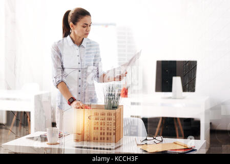 Uneployed young woman packing her belongings in the office - Stock Photo