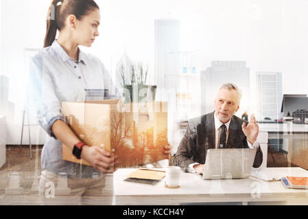 Unemployed young woman leaing her previous place of work - Stock Photo