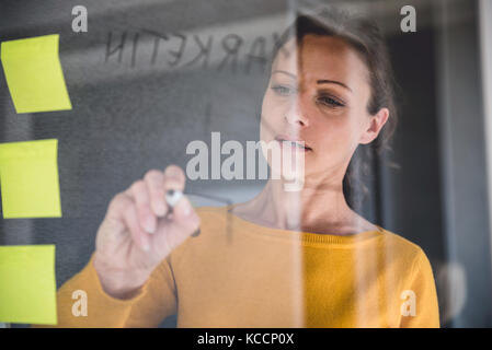 Woman writing notes on the glass board at the office - Stock Photo