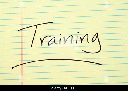The word 'Training' underlined on a yellow legal pad - Stock Photo