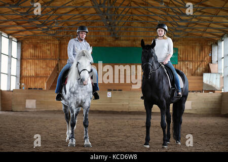 People on a horse training in a wooden arena - Stock Photo