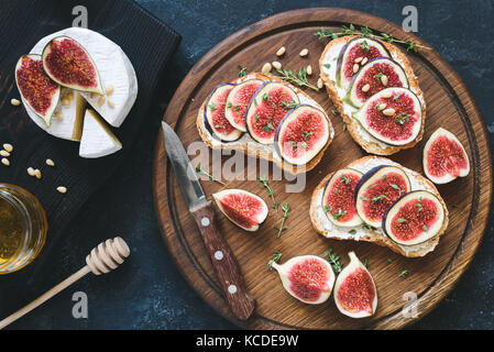 Bruschetta with fresh purple figs, ricotta cheese and honey on wooden cutting board served with brie camambert cheese - Stock Photo