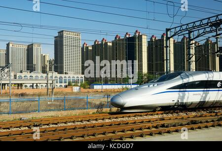 Chinese high speed electric bullet train on the Beijing rail line at Shijiazhuang Railway Station, Hebei province. - Stock Photo