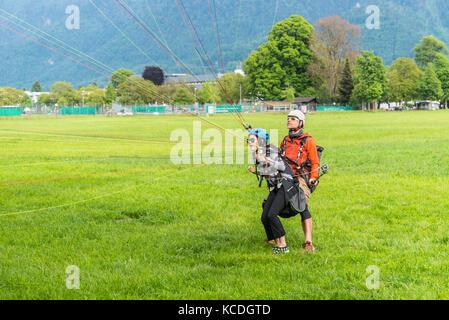Interlaken, Switzerland - May 26, 2016: Tandem paraglider on the green lawn after landing in Interlaken, Switzerland. - Stock Photo