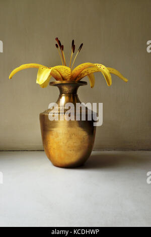 yellow lily in a vintage indian copper jar on a simple background - Stock Photo