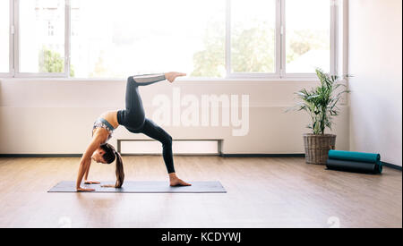 Fitness woman doing backbend stretching yoga exercise. Healthy female practicing yoga, one legged wheel pose. - Stock Photo