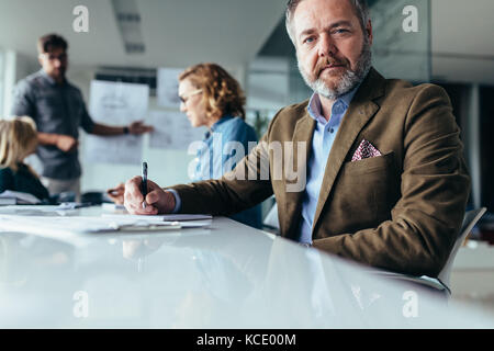 Mature businessman sitting in conference room with colleagues in background. Senior man sitting in board room during - Stock Photo