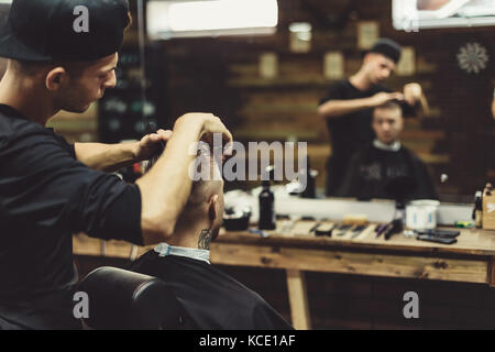 Crop barber doing haircut for client - Stock Photo