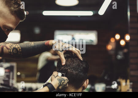 Barber shaving man in chair - Stock Photo
