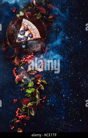 Floral border with a piece of blueberry pie, autumn leaves, berries and blue smoke on a dark wooden background. - Stock Photo
