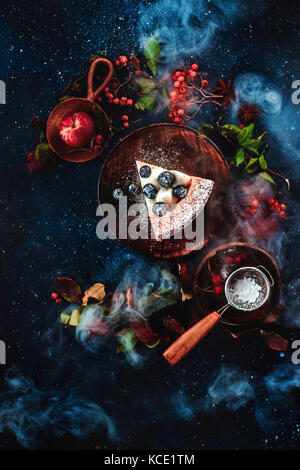 A piece of cake with powdered sugar and a strainer on a dark wooden background with floral decoration. Handmade - Stock Photo