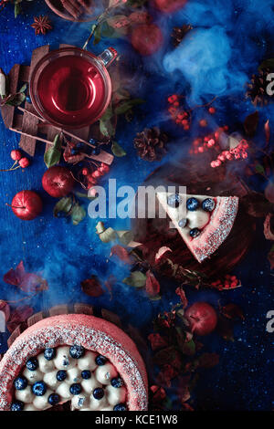 Dark autumn still life with a whipped cream blueberry cake, hot tea and floral decoration on a background with leaves - Stock Photo