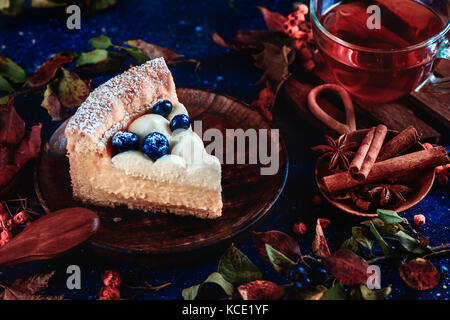 Hommemade crust cake with wipped cream, blueberries and pumpkin puree on a dark background with leaves and cinnamon. - Stock Photo