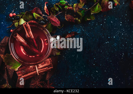 Tea cup with cinnamon on a dark background. Conceptual stylized food still life with autumn leaves and berries. - Stock Photo