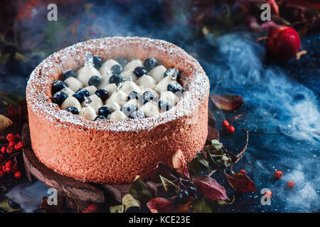 Whipped cream and blueberry cake with a shortbread crust on a dark background. Dark food photography with smoke. - Stock Photo