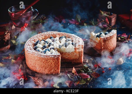 Cut cake with a shortbread crust on a dark background. A piece of cake with whipped cream and blueberries. Traditional - Stock Photo
