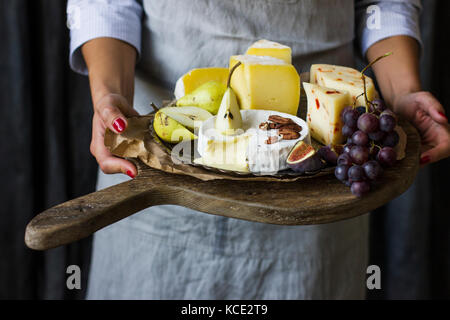 Young woman holding a plate of cheese on the wooden board - Stock Photo