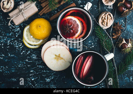 Mulled wine with apple and lemon  slices in white rural mugs  on rustic table , top view - Stock Photo