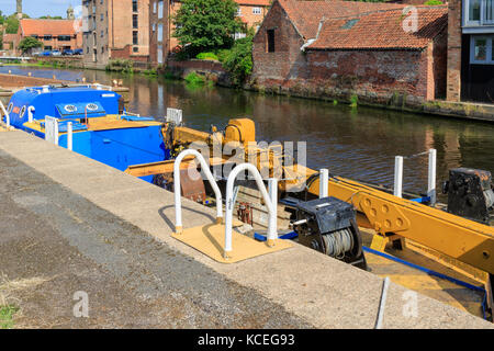 Maintenance canal barge with mounted crane moored on the River Trent. Newark-on-Trent, Nottinghamshire UK - Stock Photo