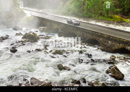 Electric car driving on bridge crossing river. Renewable energy from hydropower concept. - Stock Photo