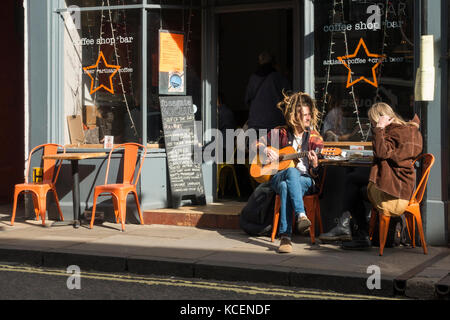 Young couple sit in sun at a table outside The Fossgate Social coffee shop & bar, York, England, UK. The man has - Stock Photo