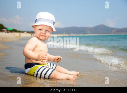 Displeased baby boy wearing hat and shorts playing on a beach - Stock Photo
