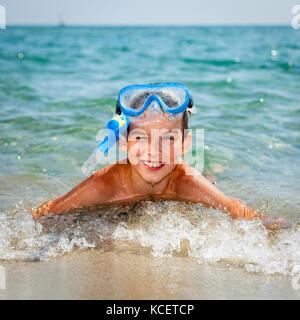 Happy boy wearing snorkeling gear lying in the sea - Stock Photo
