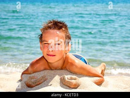 Happy boy enjoying summer day on a beach - Stock Photo