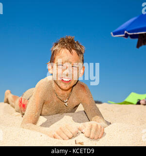 Happy boy covered with sand on a beach - Stock Photo