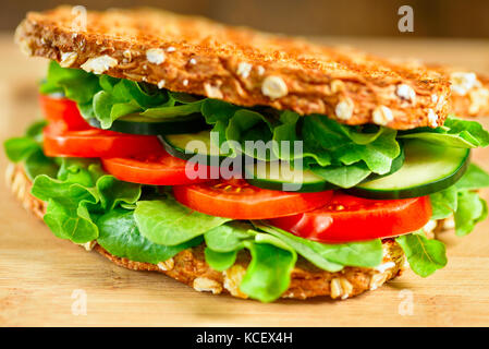 Healthy grilled vegan sandwich made of sprouted organic bread, tomato, cucumber, spinach and arugula. Selective - Stock Photo