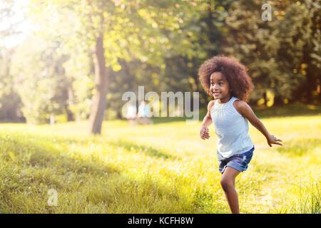 Portrait of happy little girl running on grass land - Stock Photo
