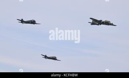 Boeing b-17 Flying Fortress and two Douglas C-47 Skytrain aircraft flying in formation at Duxford 2017 Battle of - Stock Photo