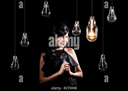 Beautiful young woman among many light bulbs - Stock Photo
