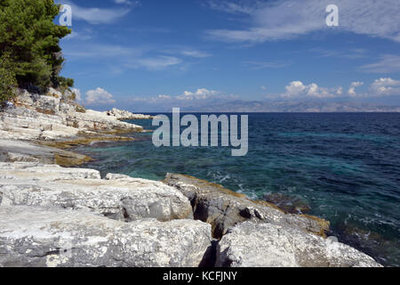 a beautiful Mediterranean rocky coastline in corfu. Crystal claeat waters on the rocky beaches at Kassiopi, Corfu, - Stock Photo