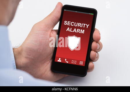 Close-up Of Businessperson Holding Mobile Phone Showing Security Alarm - Stock Photo