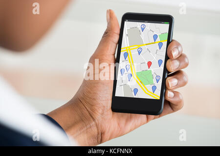 Close Up Of Woman's Hand Holding Mobile Phone With Various Location Mark On Map - Stock Photo