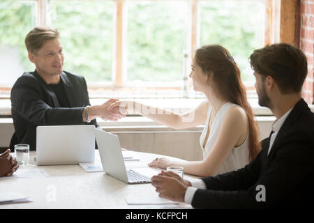 Young male executive in formal suit shaking hands with attractive female coworker. Employees greeting each other - Stock Photo
