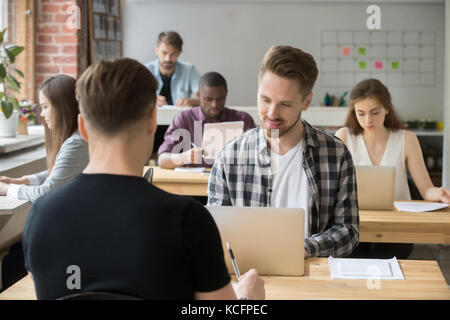 Young casually dressed employees at work in coworking office. Corporate team working on laptops and taking notes - Stock Photo