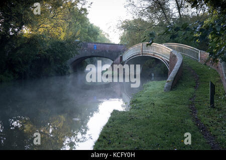 An early morning autumn mist begins rising on the Oxford Canal by Bridge 45 near Newbold on Avon. - Stock Photo