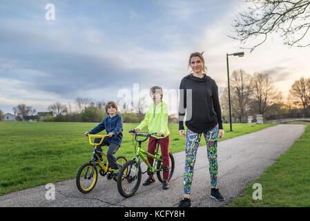 Chicago,IL,USA,April 16 2017:Mother with her two kids on bikes in park,for editorial use only - Stock Photo
