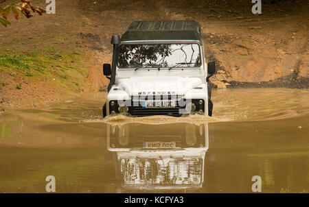 Off road 4x4 through the river in a Land Rover Defender - Stock Photo