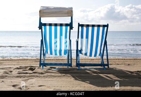 Two empty deck chairs on the beach - Stock Photo