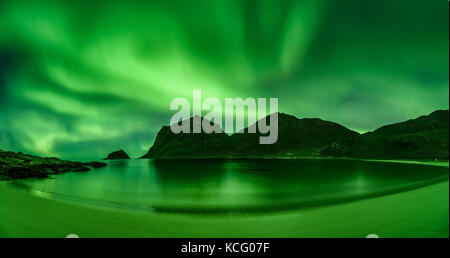Beach in the Lofoten islands in Norway with strong green norther lights - Stock Photo