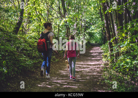 Mother and daughter walking on path in woods and talking - Stock Photo
