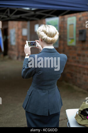 YOUNG WOMEN IN 1940'S VINTAGE RAF UNIFORM TAKING A PHOTO WITH A MOBILE PHONE, UK,2017 - Stock Photo