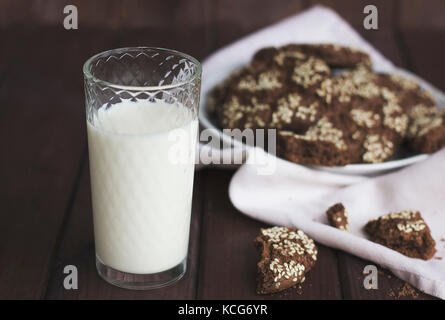 Chocolate cookies with sesame seeds in a vintage plate and a glass of milk on wooden background - Stock Photo